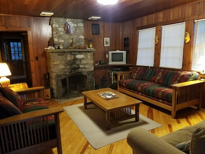 Comfortable furniture in the living room with a working wood burning fireplace.