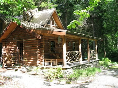 Charming cabin with covered front porch sitting area.