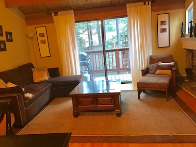 Living area and balcony with forest views