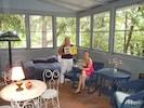 Owner & friend sharing favorite children's book on porch.