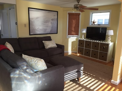 Sunny living room with new furniture and TV