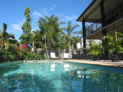 Large swimming pool, set in a tropical garden.