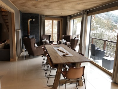 Kitchen table and seating area by fire, with access to balcony and lovely views.
