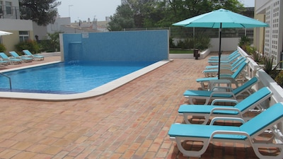 Pool area with sunbeds and Parasols