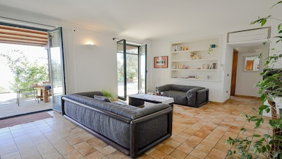 Living area room with access outdoor patio and garden-solarium pool villa amolu