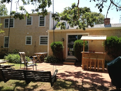 Outdoor patio features TIKI bar, hammock swing chair, picnic table and gas grill