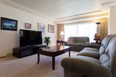"""Living room with 55"""" HDTV with blu ray player and Netflix!"""