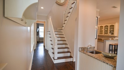 Entryway leads on to grand staircase and open concept kitchen-living-dining area