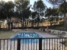 Espace piscine fermé avec cabane dans les arbres au fond