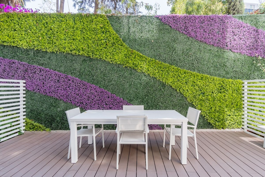 VRBO Mexico City: White table and chairs at small outdoor urban garden with wall that has grass and purple flowers