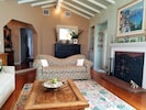 The living room has original hardwood floors, vaulted ceiling and fireplace.