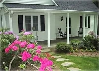 Rest in the front porch rocking chairs and enjoy the gardens