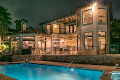 Nighttime paradise with huge pool overlooking the lake under the night sky.
