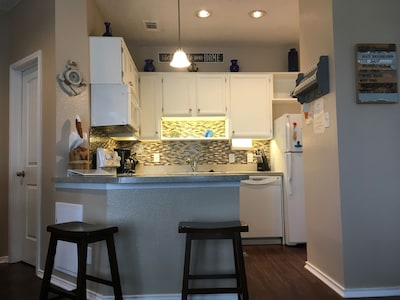 Newly updated kitchen with glass backsplash and under cabinet lighting.