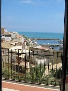 Balkon mit Blick auf Meer und Fischerhafen
