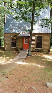 Evergreen Hideaway is a cabin nestled under tall pines.