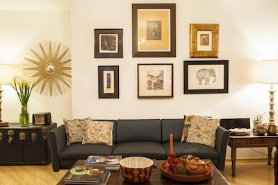 Spacious living room decorated with antiques and original art work from recognized local artists.