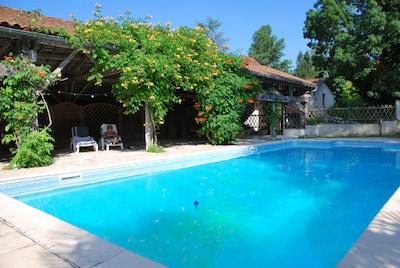 La piscine avec sa terrasse couverte