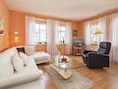 Wohn/Essbereich mit Couch, Couchtisch, Sessel und TV