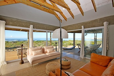 Open plan lounge with glass doors opening up to the patio with full sea views