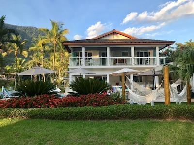 Casa de frente para o mar rodeada por natureza, dentro de condomínio fechado.
