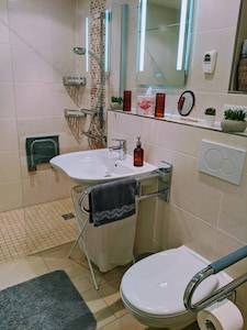 Badezimmer mit ebenerdiger Dusche und behindertengerechter Ausstattung