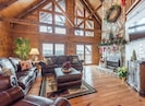 Large Great room with vaulted ceilings, Gable windows , & stone gas fireplace.