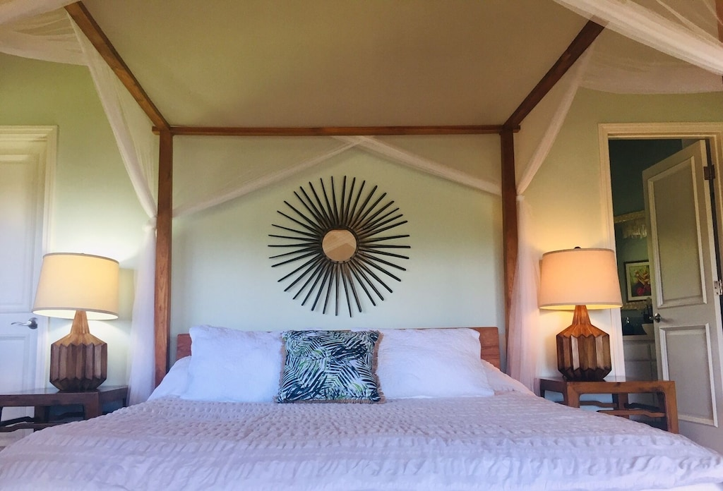Bedroom with poster-bed and sun-shaped mirror