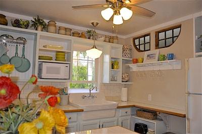 Bright charming coastal kitchen with farm sink. Antique windows over shelf.
