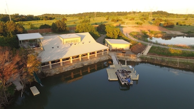 Lodge, upper deck, porch and dock with pontoon boat.