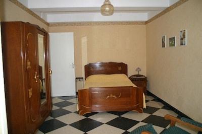 Grande chambre lit deux places, penderie et armoire de rangement.