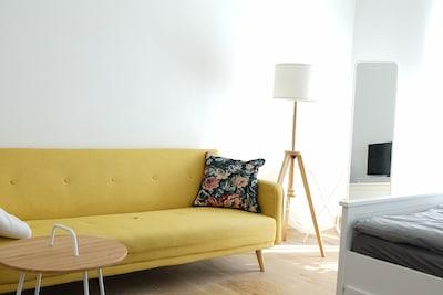 Das senffarbene Sofa im Wohn- und Schlafzimmer bietet Platz für 3 - 4 Personen