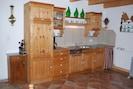 Küche mit Kühlschrank, Geschirrspüler, Filterkaffeemaschine und Kochgelegenheit.
