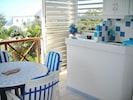 Cuisine américaine sur terrasse avec baies jalousies amovibles.
