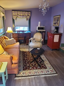 sitting area with desk, fridge, microwave, and coffeemaker.