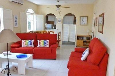 livingroom  with doors to courtyard and sunroom. Free wifi. UK TV. AIRCON.