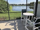 Lake view from pool area with bar height chairs and table