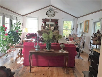 Charming, airy living room, 6 French doors (left) overlooking garden, fireplace