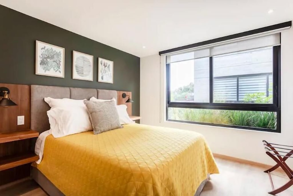 VRBO Mexico City: Bedroom with large window and yellow blanket on the bed