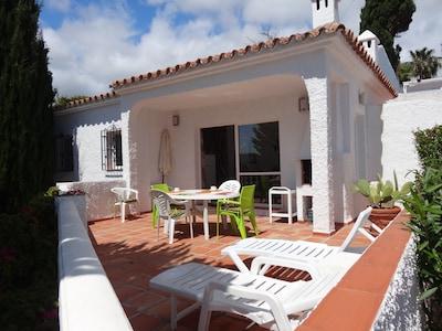 La villa vue de la terrasse avec barbecue intégré .