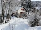 Vue d'ensemble du chalet en hiver depuis l'entrée de la propriété.