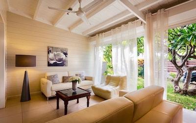 Salon en cuir cosy sous la véranda, ouvrant sur le jardin