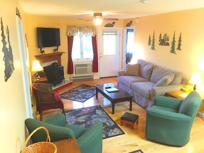 Large family room with gas stove, flat screen TV, and balcony access.