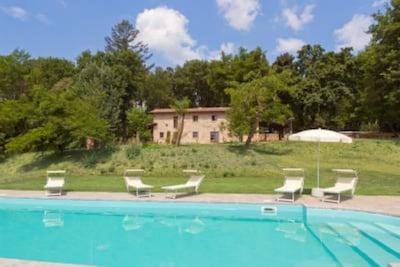 Villa mit Pool im Herzen der Toskana, umgeben von einem großen, bewaldeten Park