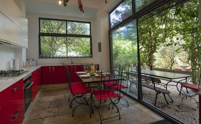 Cuisine de 25m2 avec de grandes baies vitrées sur le jardin