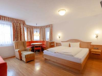 Wohnschlafraum mit großem Doppelbett, Essecke im Erker und Sitzgelegenheiten