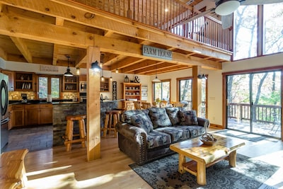 The living room opens up to kitchen and dining space and has floor to ceiling windows out into the forest.