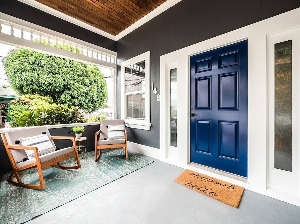 Front porch with rocking chairs and a blue front door