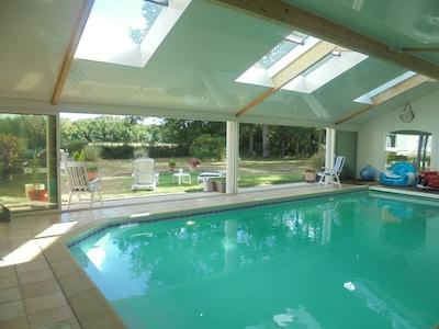 vue piscine intérieure chauffée  et donnant sur parc arrière  avec baies vitrées