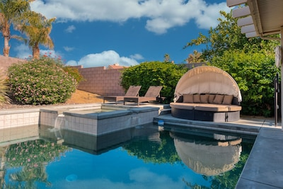 Saltwater pool, and hot tub with two lounge chairs and outdoor cabana lounge